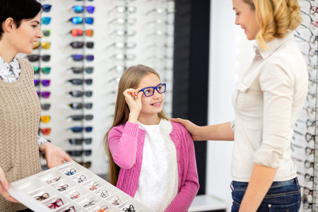 Young girl in optical shop choose new eye frames with mother