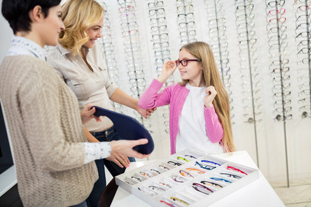 Female child try brown frame glasses in optician 写真素材