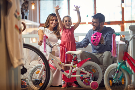 Sale, consumerism and people concept - happy family with little child and shopping new bicycle