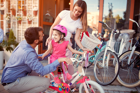 Young family with happy kid having fun outdoor shopping new bicycle and helmets