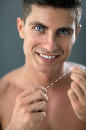 Smiling  handsome young man cleaning his teeth with dental floss