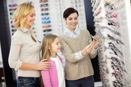 Friendly saleswoman in optician helps to female child to choose good frame for eyeglasses