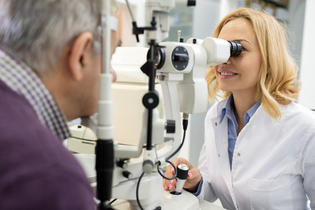 Sympathetic female eye doctor looks at patient eyes using apparatus in eyes clinic Standard-Bild - 123222272