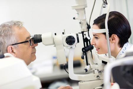 Frau beim Augenarzt, der in Ophthalmoskopapparat schaut