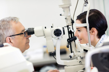 Woman at eye doctor looking in ophthalmoscope apparatus