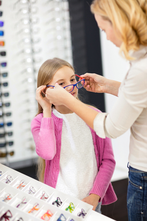 Mother in optician helps to daughter to choose appropriate frame glasses Banco de Imagens - 125131646
