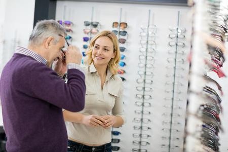 Older man in optic shop try frame glasses
