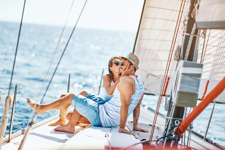 Smiling young lovers spending time together and relaxing on yacht Stock Photo