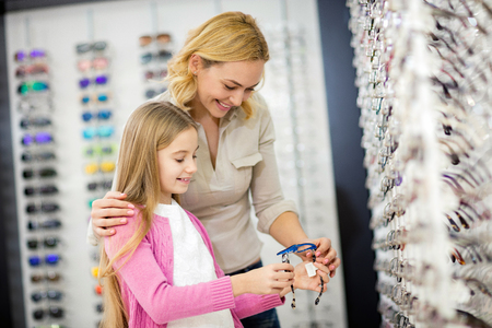 Mother and her child look at nice blue frame for eyeglasses in optician