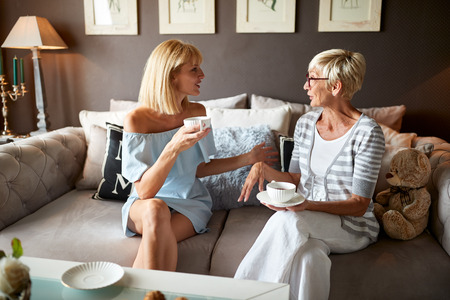 Young and elderly female talking and drinking coffee
