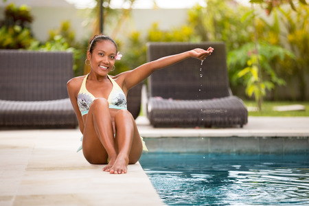 Young Asian woman spending time near swimming pool, relaxing and enjoy