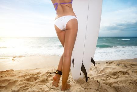 Achteraanzicht van een surfervrouw die een surfplank vasthoudt