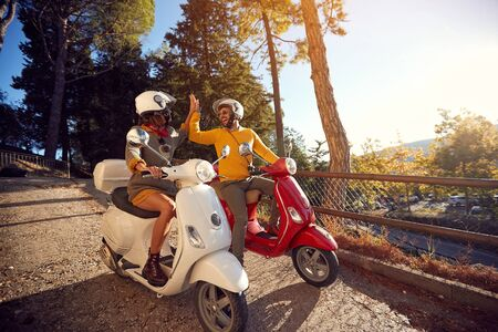 Cheerful young couple riding a scooter and having fun. Stock fotó