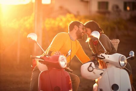 Romantic young man and woman riding on a scooter in old European.