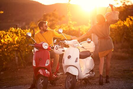 Happy young man and woman on scooter enjoying in romantic road trip. Stock fotó