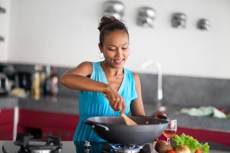 Beautiful Asian woman preparing food in wok Stock Photo