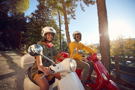 Happy woman and man traveling on motorcycle and having fun.