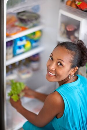 Young woman front open fridge in the kitchen Stock Photo