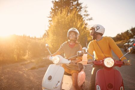 Happy young couple on scooter enjoying road trip on vacation. Stock fotó