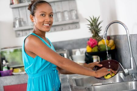 Smiling woman standing front of kitchen sink  washing dishes and looking at camera Stock Photo