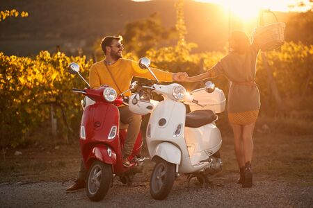 Romantic young man and woman riding on a scooter in old European on vacation.