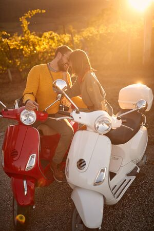 Happy young couple on scooter enjoying in romantic road trip on vacation.
