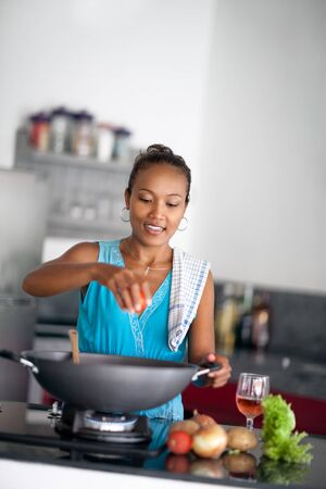 Asian housewife preparing food and squeezes tomato in meal