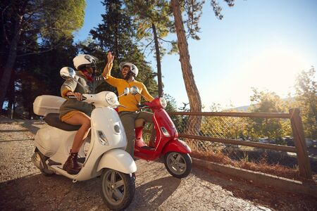 Cheerful young couple riding a scooter and looking at Italy on vacation Stock fotó