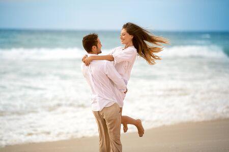 Romantische minnaars op het strand, man die zijn vriendin vasthoudt en in cirkels rent Stockfoto