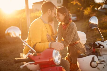 Happy young couple on scooter enjoying in romantic road trip on vacation at sunset. Stock fotó