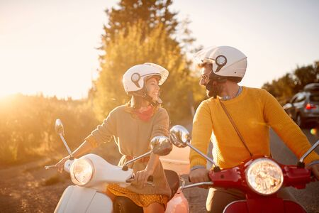 Happy young couple on scooter enjoying road trip on vacation at sunset.