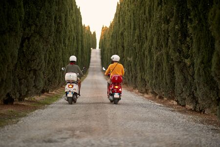 Man and woman on romantic road trip on scooter at beautiful sunset. Back view. Stock fotó