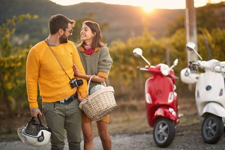 Man and woman on romantic road trip on scooter at beautiful sunset. Stock fotó