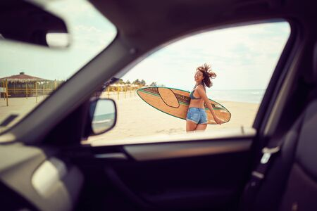 Smiling young woman surfer girl in bikini with surfboard walking on the beach.