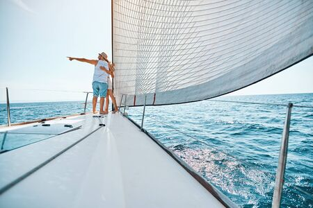 Young happy couple in love sailing sailboat yacht.