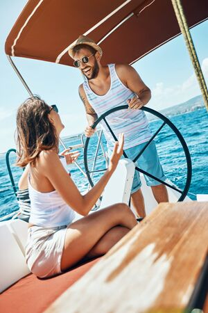 Happy man and woman having fun on a boat trip in the summer Stock Photo