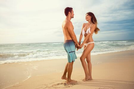 Cute young couple holding hands and stand facing each other on beach 写真素材