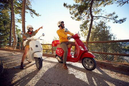 Happy young couple traveling on motorcycle and looking at Italy on vacation.