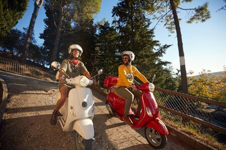 Happy young couple in love on scooter driving together.