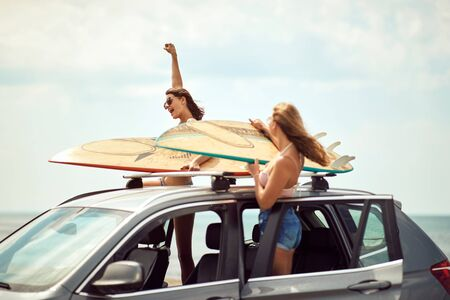 Sexy smiling surfer women's by a car getting ready for surfing Imagens