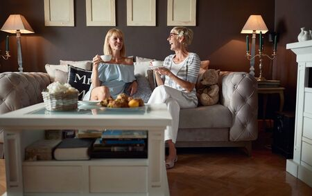 Two very cheerful women talking and drinking coffee 版權商用圖片