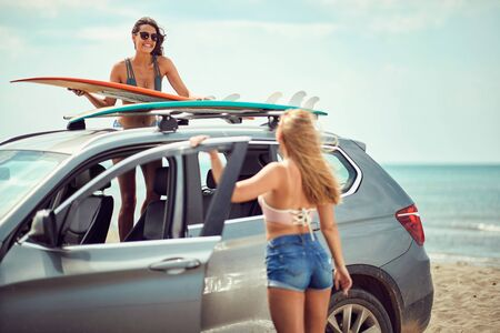 sexy smiling surfer girls by a car getting ready for surfing