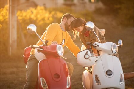 Couple on romantic road trip on scooter at beautiful sunset on vacation.