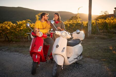 Romantic young couple riding on a scooter and enjoying on vacation at sunset. Stock fotó
