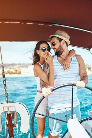 Beautiful young couple of lovers sailing on a boat