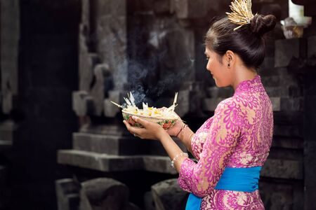 Balinese woman with gods offerings in traditional ceremonial clothing