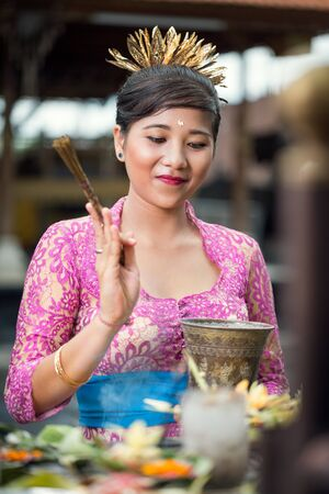 Young pretty woman in traditional ceremonial clothing praying at Hindu temple Stock Photo
