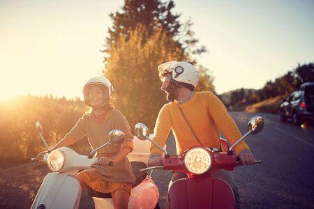 Feliz pareja joven en scooter disfrutando de viaje por carretera