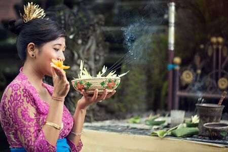 praying woman offers flowers to Gods, Bali, Indonesia Stock Photo