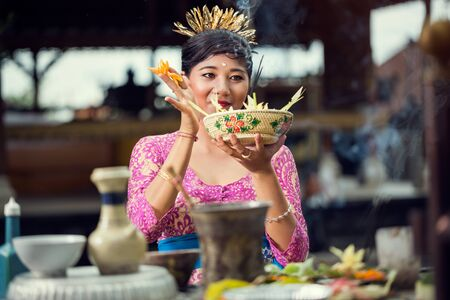 Smiling Balinese woman in a pink dress making flower offerings to the Gods at a Hindu temple Stock Photo